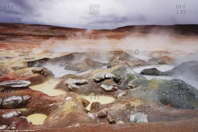 Steam emitting hot spring on volcanic landscape