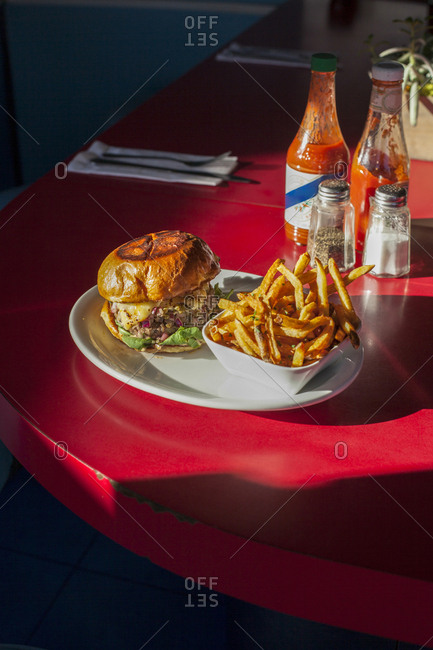 High angle view of burger with French fries served in plate on table at restaurant