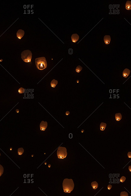 Low angle view of illuminated Chinese lanterns flying against sky at night