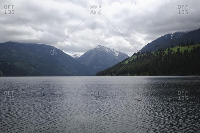 Scenic view of Wallowa Lake by mountains against cloudy sky