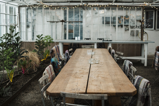 Chairs arranged by wooden table at greenhouse