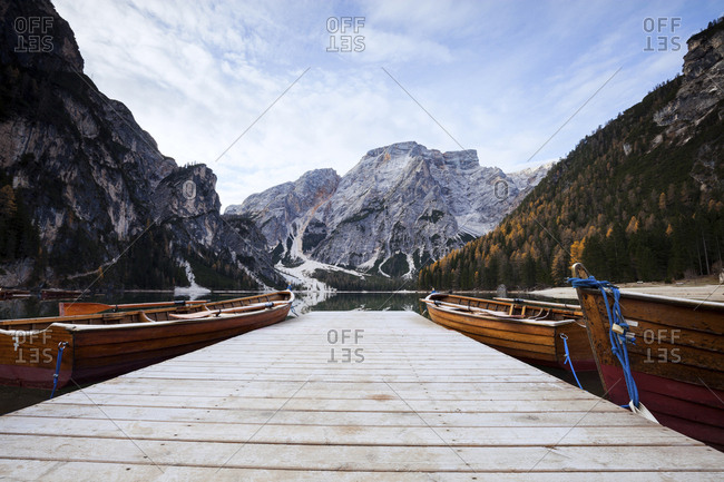 Boats moored by pier on Lake Braies by mountains against sky during winter