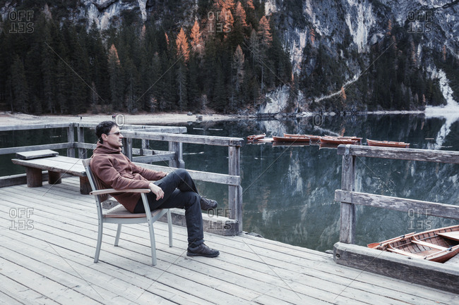 Beautiful view of a young man sitting on wooden chair