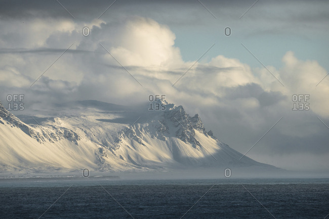 Scenic view of sea by snowcapped mountain against cloudy sky