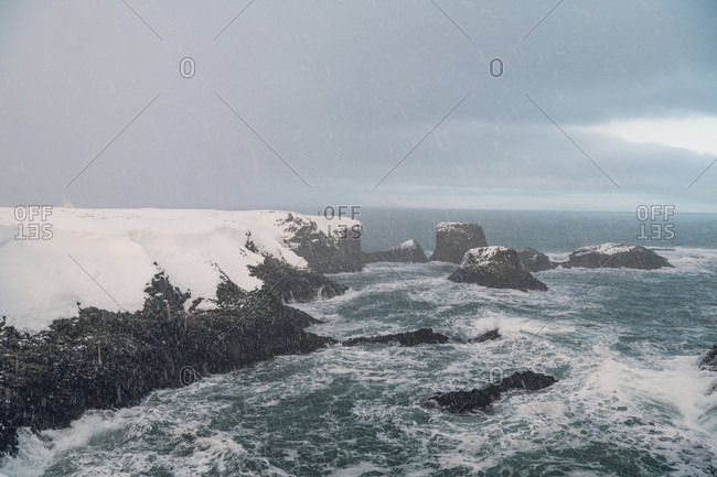 Scenic view of sea by mountain against cloudy sky during snowfall