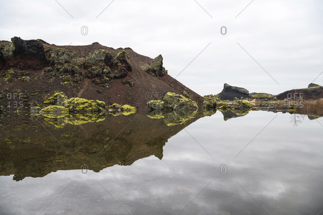 Scenic view of calm lake by rock formations against cloudy sky