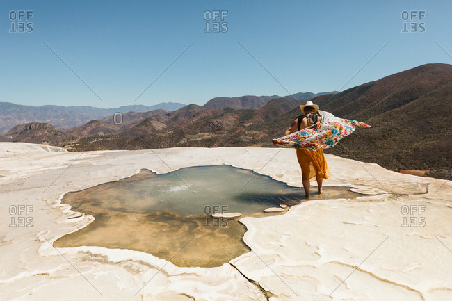 young woman in colorful skirt and scarf walks in a hot spring