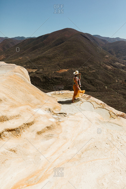 tourist stands on the edge of a limestone cliff in oaxaca mexico