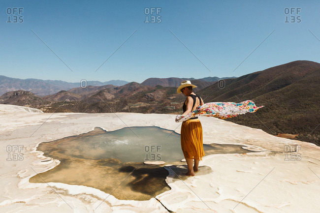 scarf blows in wind at the edge of a hot spring at hierve del agua