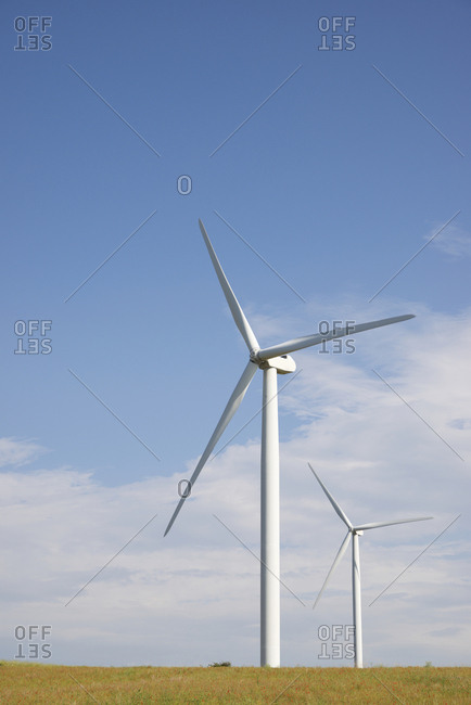 Windmills on field against blue sky during sunny day