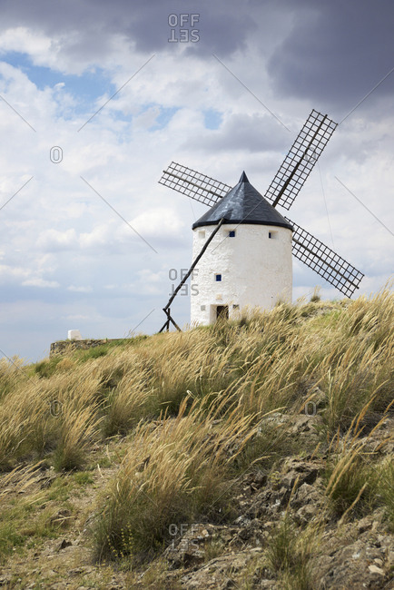 Low angle view of Traditional Windmill on hill against cloudy sky during sunny day