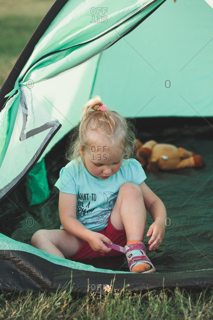 Little girl playing in tent at campsite during vacation