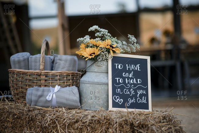 Sheets in wicker basket with flowers and blackboard on hay bale at wedding ceremony