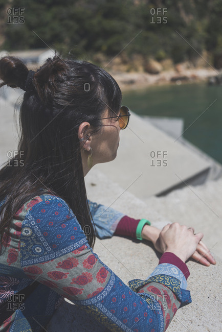 Woman looking at view by retaining wall during sunny day