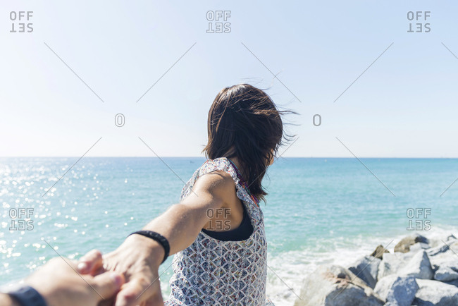 Portrait of happy young woman holding hand on the beach