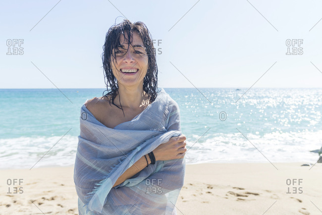 Close-up of a young woman covered with a towel while looking camera