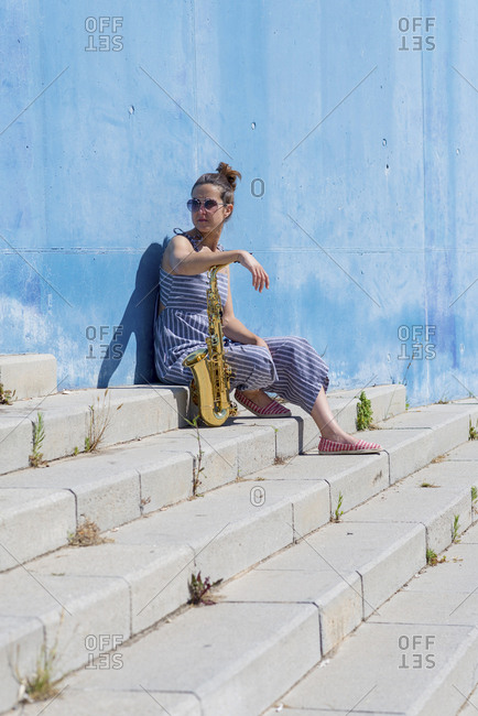 Side view of a woman sitting and leaning on wall, holding a saxophone