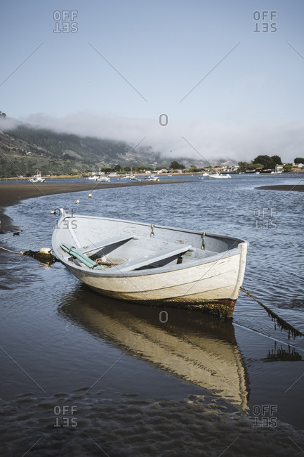 Empty tied up row boat sits on sand at low tide in Bolinas, California
