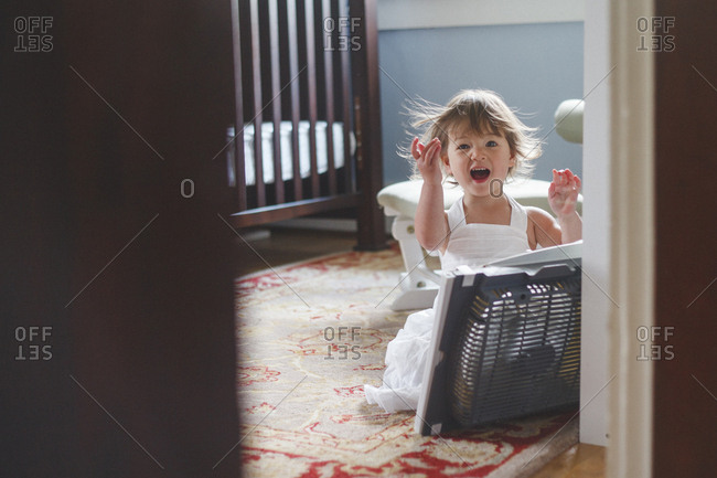Portrait of cute baby girl with mouth open enjoying breeze from electric fan at home seen through doorway