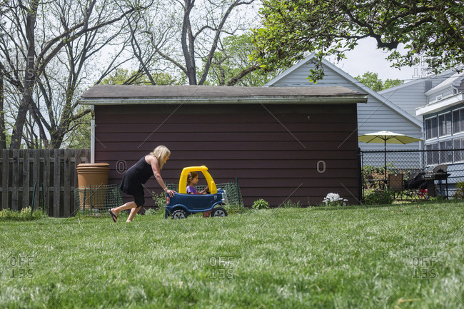 Side view of playful grandmother pushing granddaughter sitting in toy car on grassy field at yard