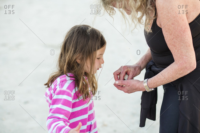 Side view of grandmother showing seashells to granddaughter while standing at beach