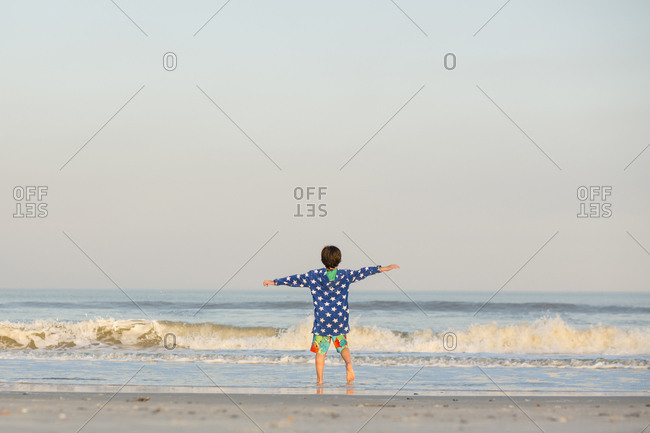 Rear view of boy with arms outstretched standing at shore against clear sky during sunset