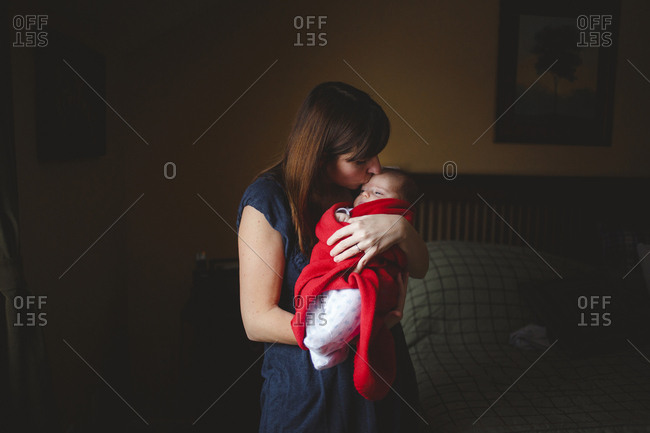 Mother kissing cute daughter while carrying her in bedroom at home