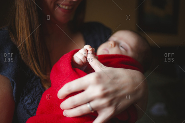Close-up of cute daughter holding mother's finger while standing at home