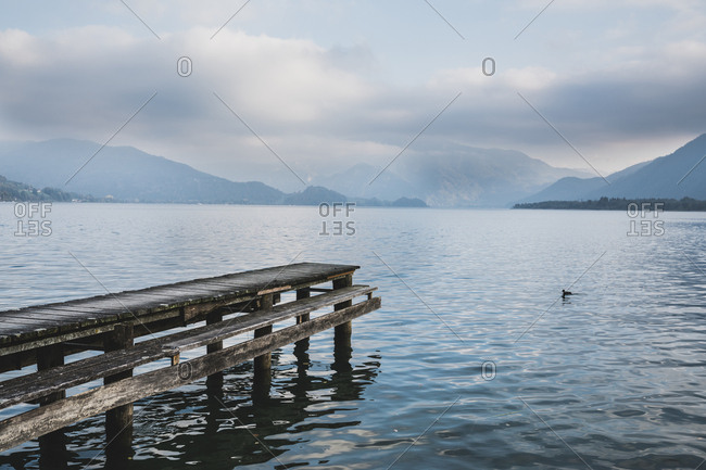 Pier over Mondsee lake against cloudy sky