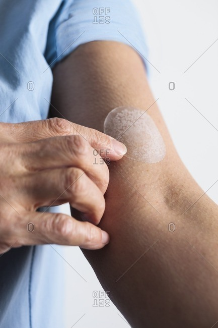 Woman applying a hormone replacement therapy (HRT) patch to her arm.