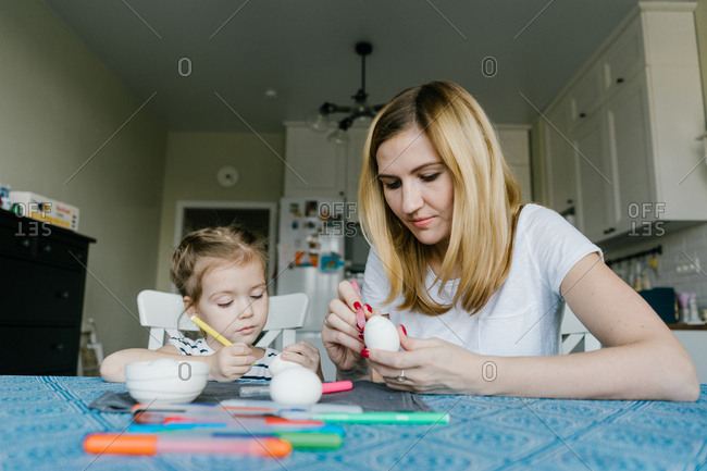 Mother and child decorate an Easter egg. girl with mother to draw egg