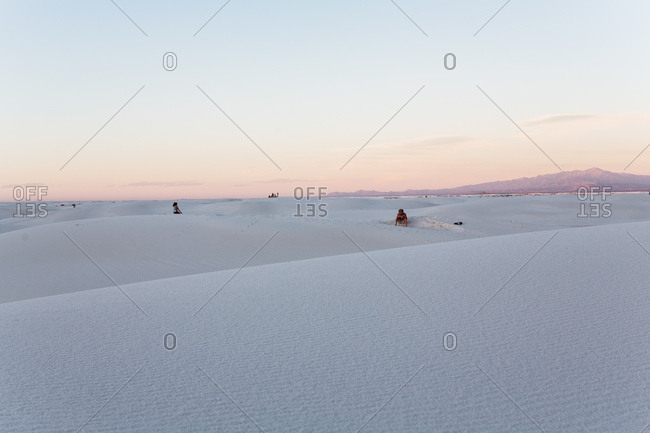 two people in the distance on dunes at sunset with mountains in back