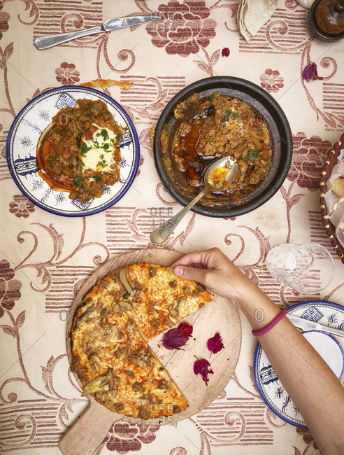 High Angle View of Traditional Morocco food and hand holding the pizza