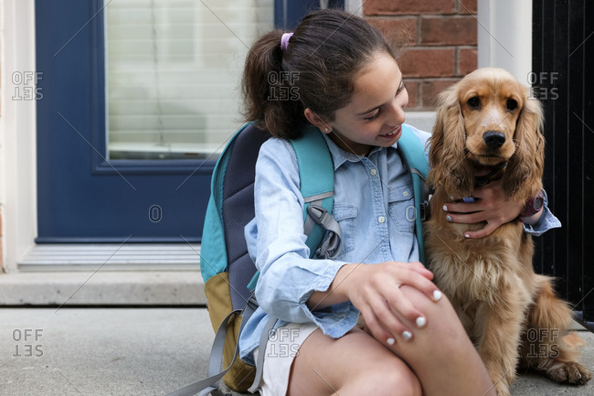Smiling girl with backpack sitting by Cocker Spaniel on porch