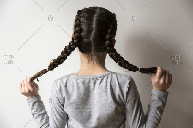 Rear view of girl holding her French braided pigtails while standing by wall at home