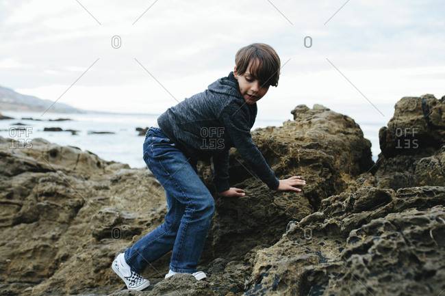 Side view of boy climbing on rocks by sea at Yosemite National Park