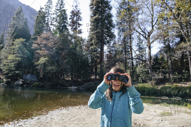 Girl looking through binoculars while standing on lakeshore in forest at Yosemite National Park