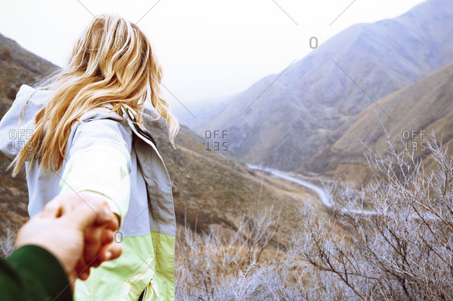 Couple holding hands and exploring mountain area