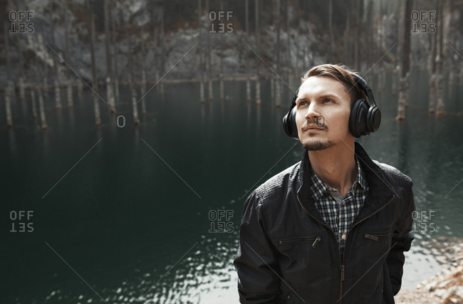 Young man wearing headphones and listening music at the mountain lake