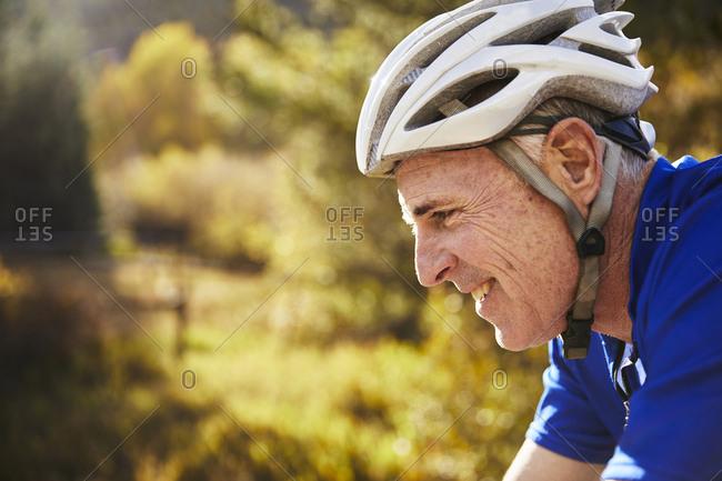Side view of smiling senior man wearing bicycle helmet