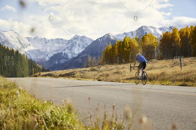 Senior man riding bicycle on country road against mountain range
