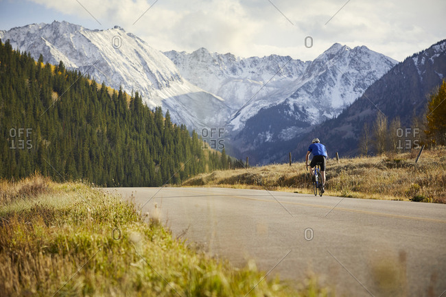 Rear view of senior man riding bicycle on country road against mountain range