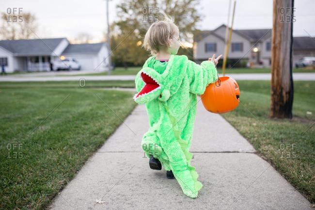 Toddler girl dressed as an alligator carrying Halloween bucket