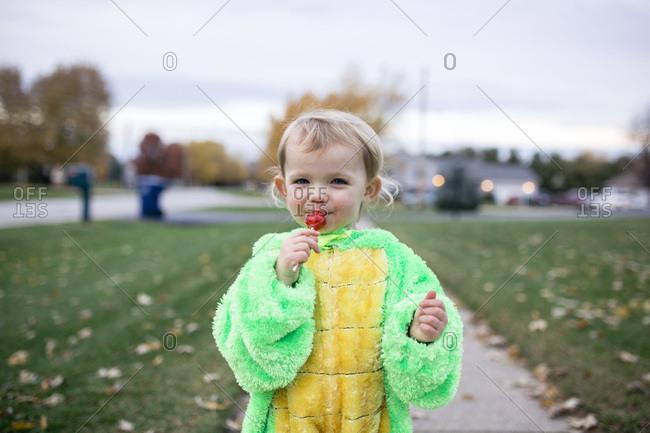 Happy toddler girl eating red sucker on sidewalk on Halloween