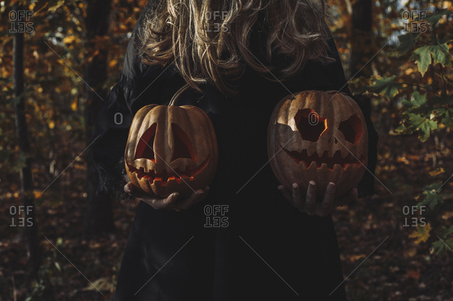 Midsection of spooky woman holding jack o' lanterns in forest during Halloween