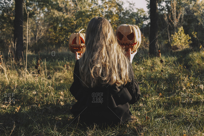 Rear view of woman holding jack o' lanterns while sitting on grassy field in forest during Halloween