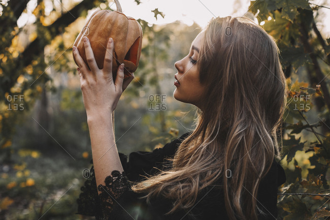 Side view of young woman looking at jack o' lantern in forest during Halloween