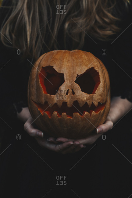Midsection of woman holding spooky jack o' lantern in forest during Halloween