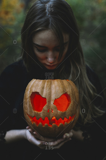 Young woman holding illuminated jack o' lantern while standing in forest during Halloween