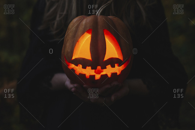 Close-up of woman hands holding illuminated jack o' lantern in forest during Halloween